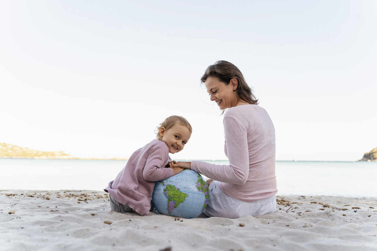 Portrait of happy little girl sitting with her mother on the beach playing with Earth beach ball - DIGF08830 - Daniel Ingold/Westend61