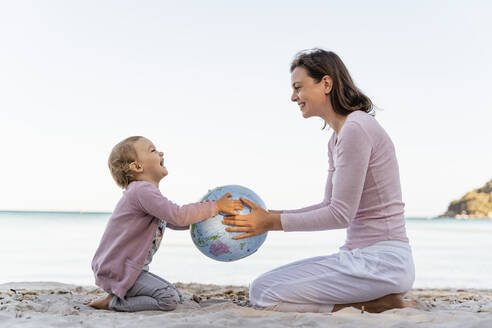Happy little girl sitting with her mother on the beach playing with Earth beach ball - DIGF08833