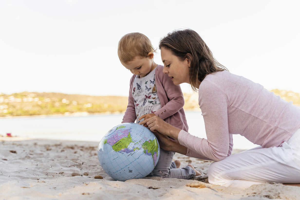 Mother and little daughter on the beach looking together at Earth beach ball - DIGF08839 - Daniel Ingold/Westend61