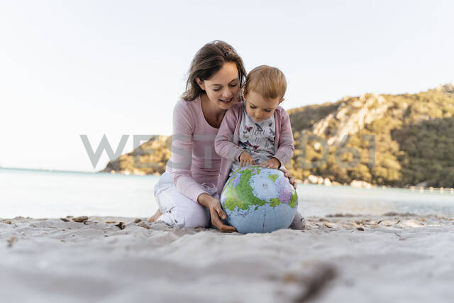 Mother and little daughter looking together at Earth beach ball - DIGF08845 - Daniel Ingold/Westend61