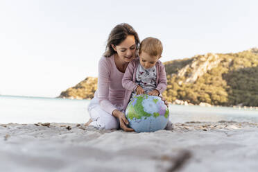 Mother and little daughter looking together at Earth beach ball - DIGF08845