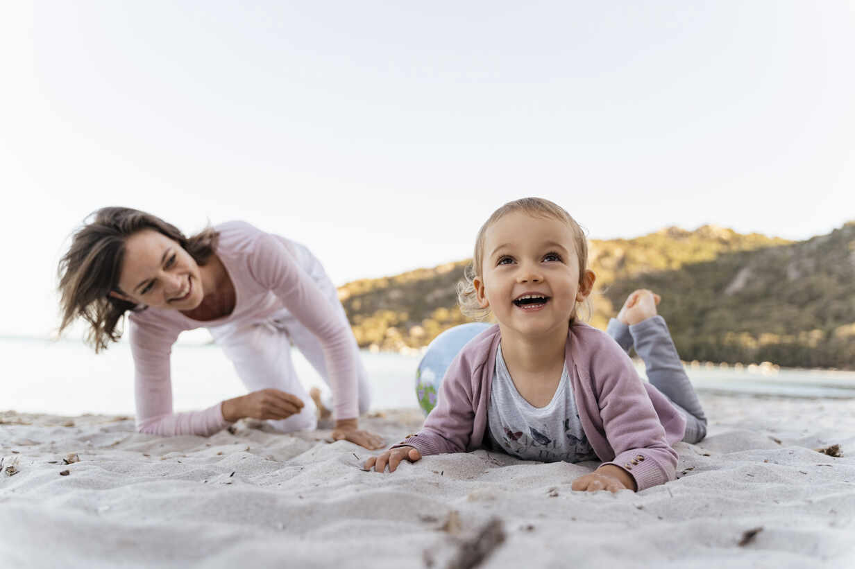 Portrait of smiling happy girl on the beach with mother watching her from the background - DIGF08848 - Daniel Ingold/Westend61