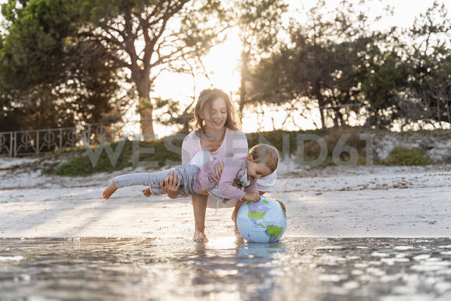Mother and little daughter playing together with Earth beach ball at seashore - DIGF08851 - Daniel Ingold/Westend61