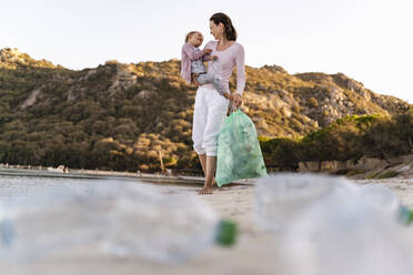 Woman on the beach carrying little daughter on her arm collecting empty plastic bottles - DIGF08857