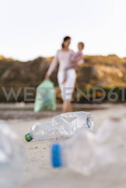 Woman with children on her arm collecting empty plastic bottles on the beach - DIGF08860 - Daniel Ingold/Westend61