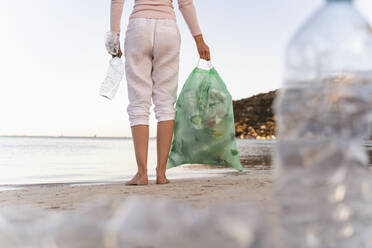 Back view of woman standing on the beach with bin bag of collected empty plastic bottles - DIGF08866