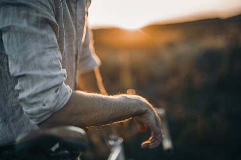 Close up of a young man with his racing bicycle in sunshine - MKF00010