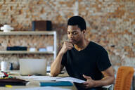 Young man sitting at table looking at notebook - SODF00119