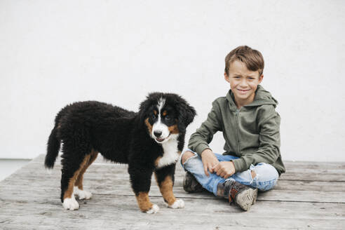 Boy playing with his Bernese mountain dog in the garden - HMEF00675