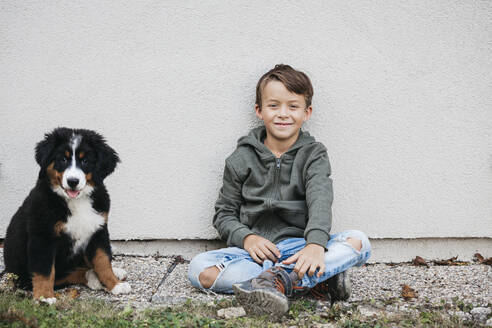 Boy playing with his Bernese mountain dog in the garden - HMEF00678