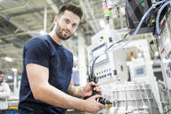 Portrait of a confident man working in a modern factory - WESTF24263