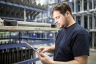 Worker using tablet in factory warehouse - WESTF24272