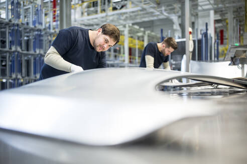 Two colleagues examining bonnet in car factory - WESTF24281