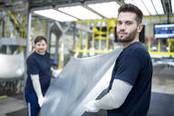 Two colleagues carrying bonnet in car factory - WESTF24287