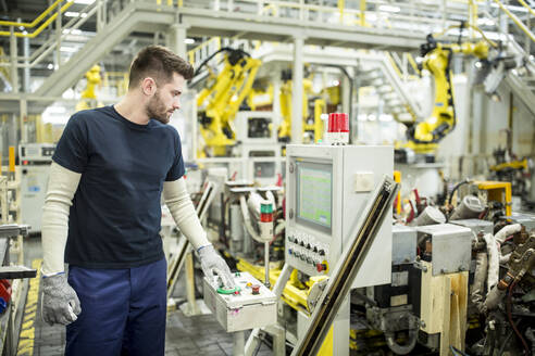 Man working in a modern factory operating a machine - WESTF24305
