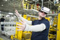 Man wearing VR glasses in modern factory - WESTF24320