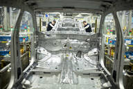 Two colleagues working in modern car factory - WESTF24332