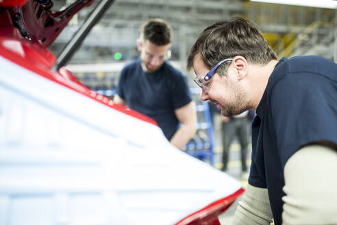 Two colleagues working in modern car factory - WESTF24356