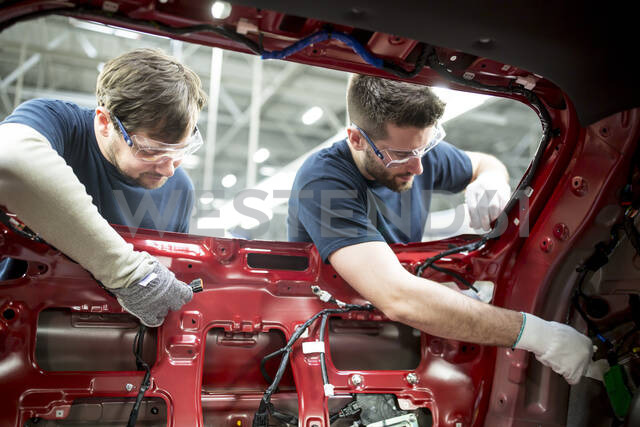 Two colleagues working at bodywork in modern car factory - WESTF24359 - Fotoagentur WESTEND61/Westend61