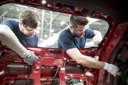 Two colleagues working at bodywork in modern car factory - WESTF24359