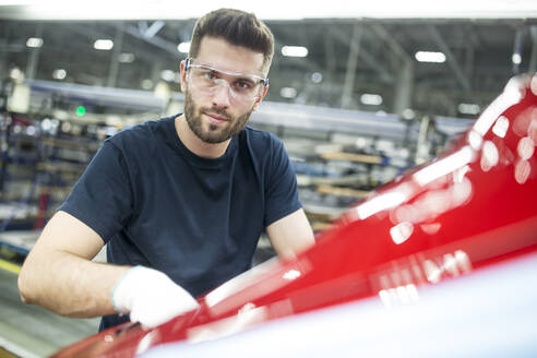 Portrait of confident man working in modern car factory - WESTF24362