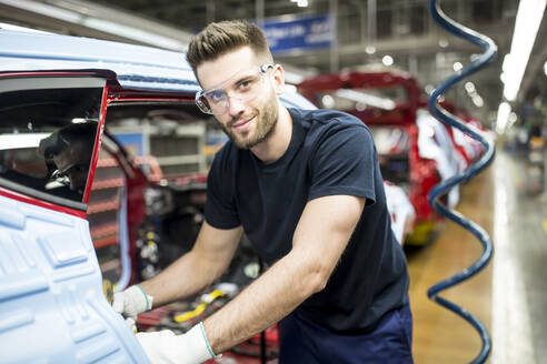 Portrait of confident man working in modern car factory - WESTF24368