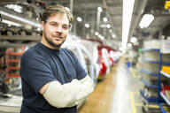 Portrait of confident worker in modern car factory - WESTF24371