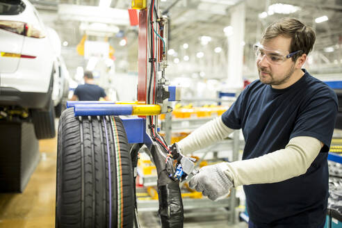 Man working on tyre in modern car factory - WESTF24383