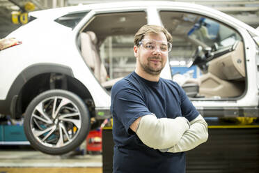 Portrait of confident worker in modern car factory - WESTF24386