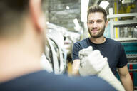 Two colleagues shaking hands in modern car factory - WESTF24389