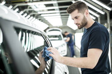 Man working in modern car factory wiping finished car - WESTF24401