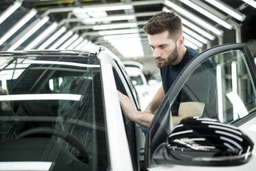Man working in modern car factory wiping finished car - WESTF24404