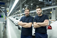 Portrait of confident colleagues in modern car factory - WESTF24413