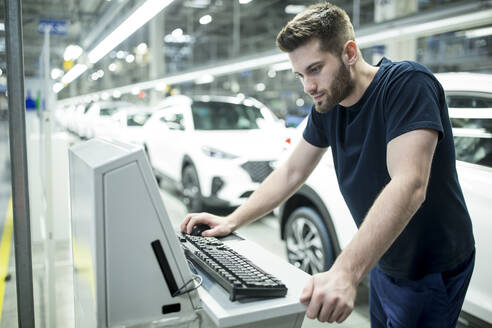 Man working on computer in modern car factory - WESTF24416