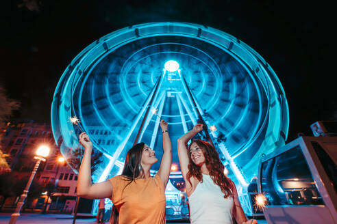 Two friends with sparkles in front of illuminated big wheel at night - MTBF00087