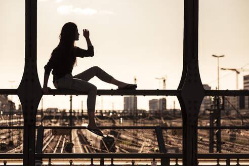 Young woman sitting on Hacker bridge at sunset, Munich, Germany - WFF00124