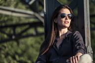 Young woman enjoying the evening sun, sitting on a bridge - WFF00130