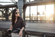 Young cyclist on a bridge at sunset - WFF00133