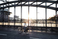 Young cyclist on a bridge at sunset - WFF00139