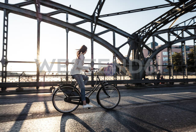 Young cyclist on a bridge at sunset - WFF00142 - Wilfried Feder/Westend61
