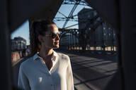 Young woman on a bridge in the evening light, seen through bridge pier - WFF00145