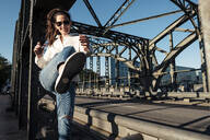 Young woman with sunglasses kicking in the air on a bridge in the evening light - WFF00148