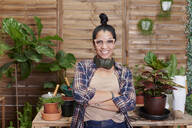 Portrait of a smiling young woman gardening on her terrace - IGGF01388