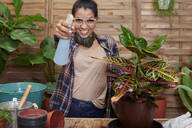 Portrait of a smiling young woman gardening on her terrace - IGGF01391