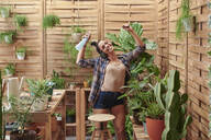 Happy young woman dancing on her terrace while gardening - IGGF01394