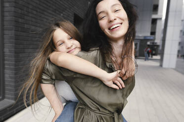 Portrait of happy mother giving her daughter a piggyback ride - EYAF00635