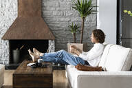 Relaxed man sitting on couch at home using tablet - GIOF07473