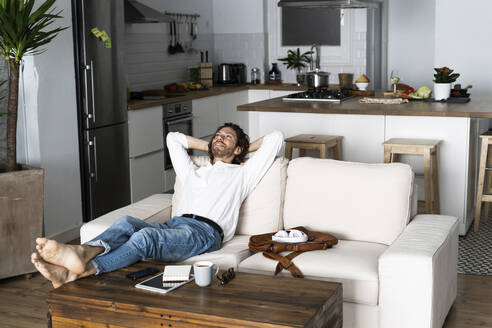 Relaxed man leaning back on couch at home - GIOF07482