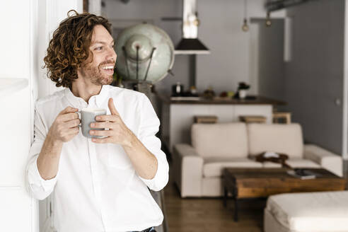 Happy man drinking coffee at home - GIOF07494