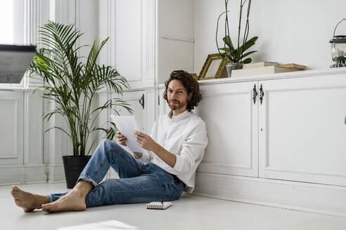Portrait of man sitting on the floor at home reviewing papers - GIOF07500